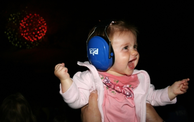 Baby with earphones during fireworks